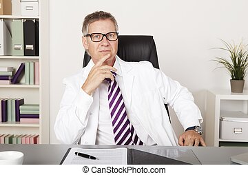 Serious Middle Age Medical Specialist Sitting Down While...