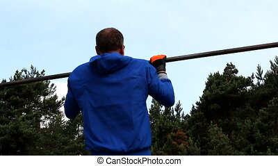 Man doing pull-ups outdoors
