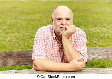Portrait of smiling old man in the park - Portrait of...