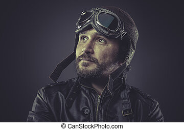 wartime pilot dressed in vintage style leather cap and...