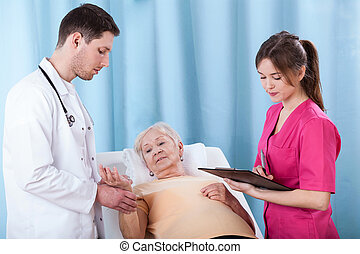 Doctors diagnosing elderly woman
