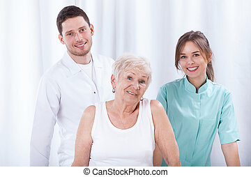 Geriatric patient with her physiotherapists - Happy...