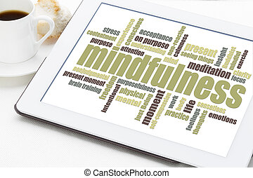 mindfulness word cloud on a digital tablet with a cup of...