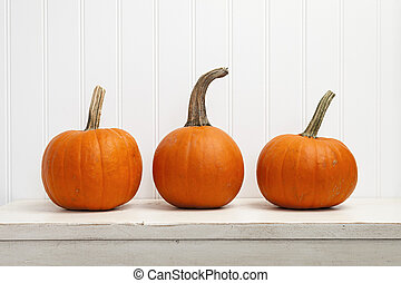 Three pumpkins - Three small pumpkins in a row against white...