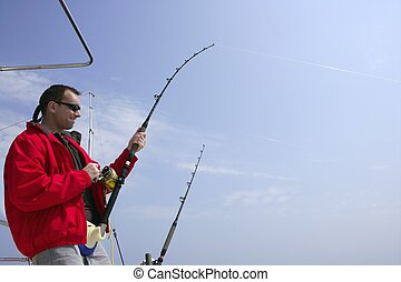 Fisherman fishing on boat big game tuna, blue sunny sky