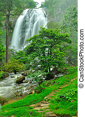 Waterfall with a pathway in green garden at Khlong Lan...