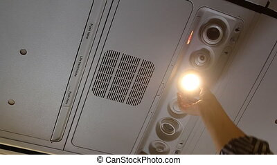 Passenger adjusting aircraft light - Airplane passenger hand...