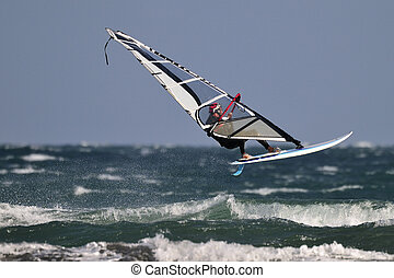 Windsurfing - Extreme windsurfer jumping high over the wave.