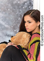 Portrait of pretty girl in sweater holding toy. Sad girl...