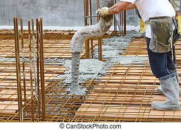 Workers pouring concrete on big floor construction on the...