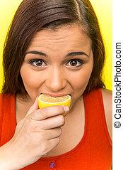 pretty girl eating fresh lemon. beautiful girl isolated on...