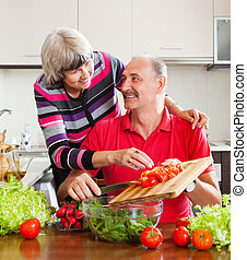 elderly couple cooking  in kitchen at home