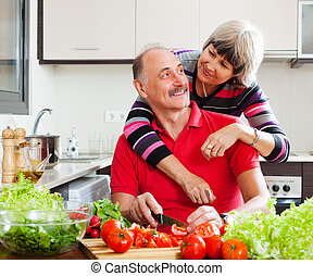 happy elderly couple cooking  in home kitchen