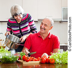 happy married mature couple cooking with tomatoes in kitchen...