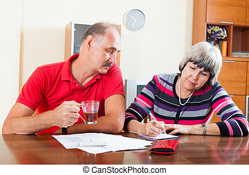serious senior couple calculating family budget - serious...