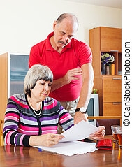 mature couple calculating family budget - serious mature...