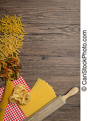 Uncooked italian pasta, brown wood table background