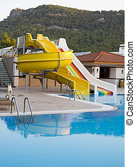 Colorful waterslides in water park pool and mountain