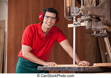 Confident Carpenter Using Bandsaw To Cut Wood - Portrait of...