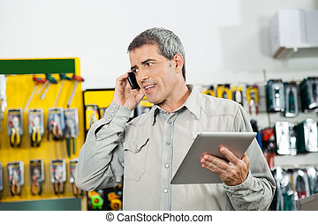 Man Holding Digital Tablet While Using Mobilephone - Mature...