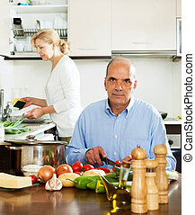 mature man helping his wife in household work - ordinary...
