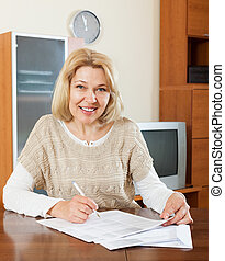 mature woman with  documents at table