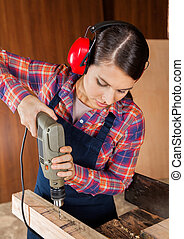 Carpenter Using Drilling Machine On Wood - Young female...