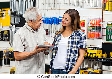 Family With Digital Tablet In Hardware Shop - Father and...