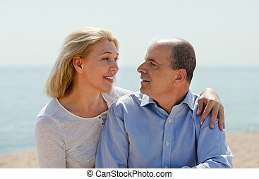 Elderly couple at sea shore - Senior mature couple having...