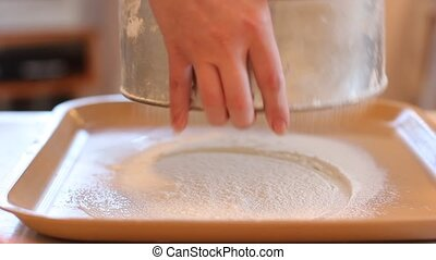 Girl sifts the flour through a sieve