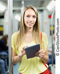Female using ereader in subway train at metro