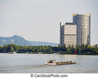 river and skyscraper Bonn - river Rhine with cargo ship and...