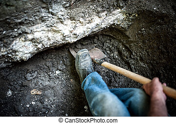 man with shovel working at a hole in the ground