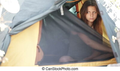 Morning in tent - Beautiful girl opens tent and yawns