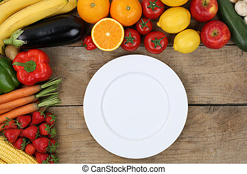 Empty plate framed with vegetables and fruits