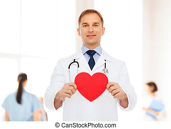 smiling male doctor with red heart and stethoscope -...