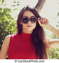 Female model in sunglasses looking outdoors. Closeup portrait