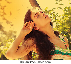 Freedom and happiness. Beautiful woman joy on bright sun light background with closed eyes