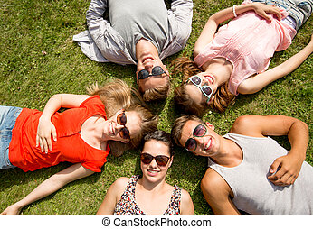 group of smiling friends lying on grass outdoors -...