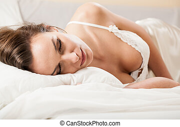 Woman sleeping in sexy underwear in bed