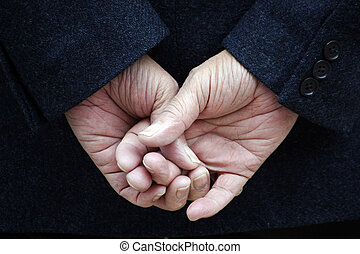 crossed fingers - Dark blue jacket and two hands with...