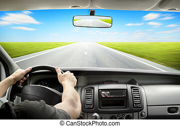 Driving - Man's hands of a driver on steering wheel of a...