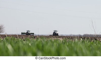 gray tractor go on black earth field - two gray tractor with...
