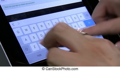 Typing on tablet keyboard - Two hands of a woman or girl...