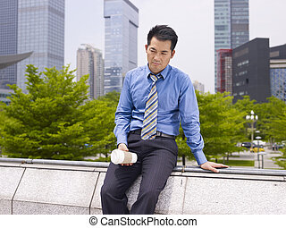 frustrated asian business executive sitting in city park.