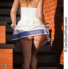 Coquettish young beautiful woman posing near the stairs at...