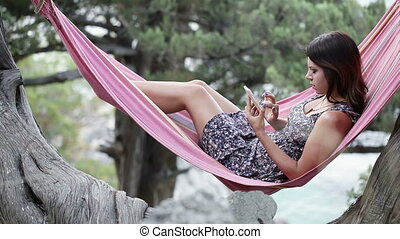 Girl in hammock smartphone - Lying in hammock girl speaks on...