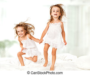 happy family . kids twin sisters jumping on the bed, playing...