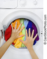 woman loading colorful laundry in the washing machine -...