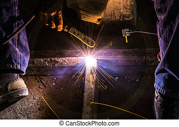 welding steel  - Worker are welding steel on low light.